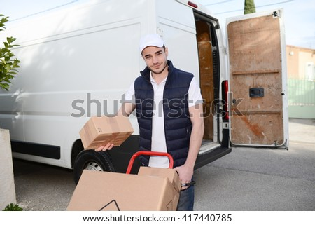 young delivery parcel service man with his commercial van on background - stock photo