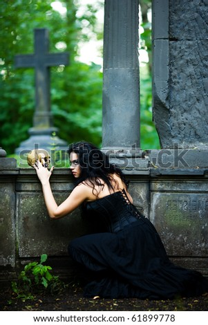 Young demonic female creature holding scull walking from crypt - stock photo