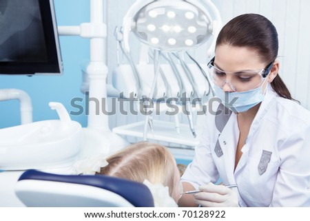 Young dentist at work in the office - stock photo