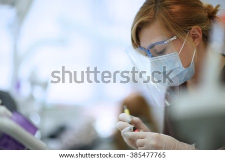 Young dentist squeezing out filling material - stock photo