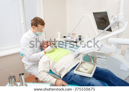 Young dentist without assistant treating elderly man - stock photo