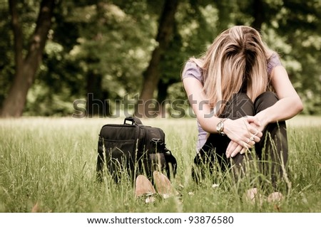 Young depressed business woman siting in grass - notebook bag and shoes lying next - stock photo