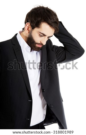 Young depressed businessman holding his head. - stock photo