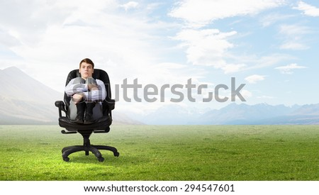 Young depressed businessman sitting in chair isolated from world - stock photo