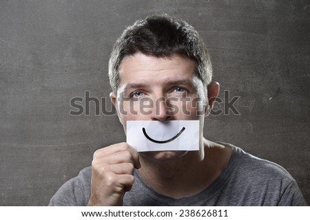 young depressed man lost in sadness and sorrow holding paper with smiley on his mouth as society forcing him to hide his pain in depression and lost of hope concept