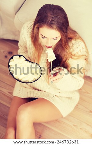 Young depressed woman is eating big bowl of ice creams - stock photo
