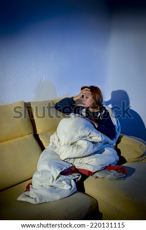 young depressed woman lying on couch wrapped in duvet and blanket feeling miserable and ill couching and suffering a cold at home in studio edgy extreme shadow lighting - stock photo