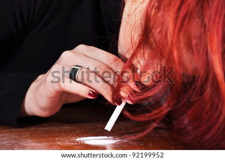 Young depressed woman snorting narcotics - stock photo