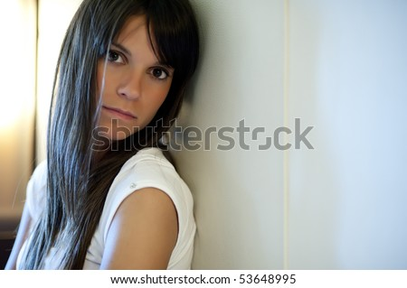 Young depressed woman staring at camera - stock photo