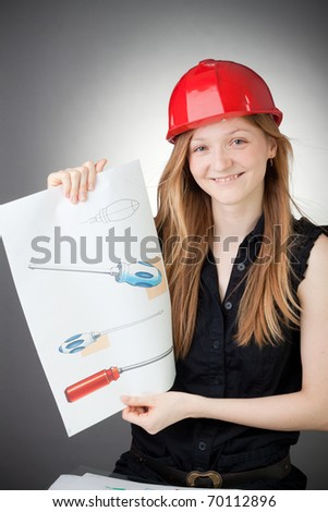 Young Design Engineer Woman Shows a Design Plan, with Grey Background - stock photo