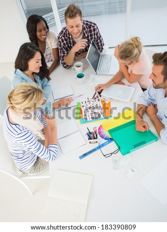Young design team going over contact sheets together in creative office - stock photo