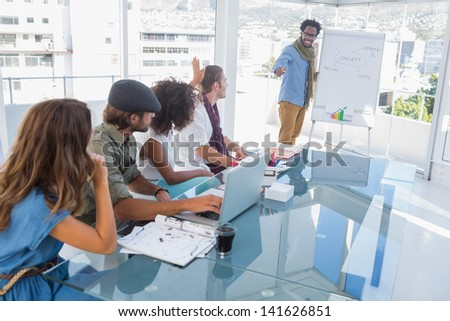 Young designer presenting a flow chart to colleagues during a meeting - stock photo