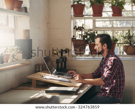 Young designer typing on his laptop while sitting in a creative space that he uses as his office in his studio  - stock photo