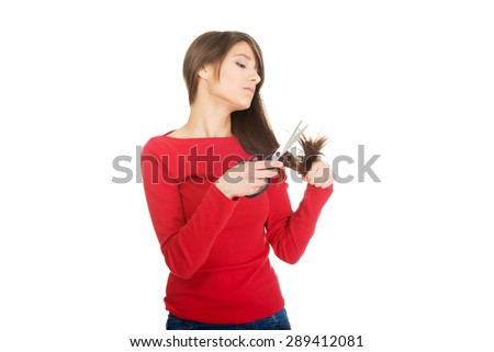 Young despair woman cutting her hair. - stock photo