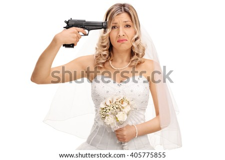 Young desperate bride holding a gun against her head and looking at the camera isolated on white background - stock photo