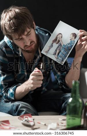 Young desperate heartbroken guy destroying love photos  - stock photo