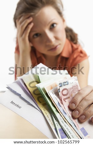 Young, desperate-looking woman holding euro notes and invoice in the camera - stock photo