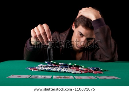 Young desperate man gambling his car in texas hold'em poker game - stock photo