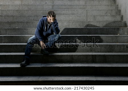 Young desperate man in casual clothes abandoned lost in depression sitting on ground street concrete stairs suffering emotional pain, sadness, looking sick in grunge lighting - stock photo