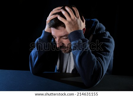 young desperate man suffering breakdown with hands on head in deep depression , pain, emotional disorder, grief and desperation concept isolated on black background with edgy grunge studio lighting  - stock photo