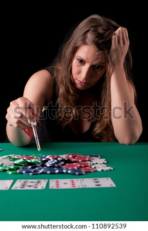 Young desperate woman gambling her house in texas hold'em poker game - stock photo