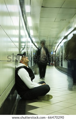 young despered guy sitting in subway tunnel - stock photo