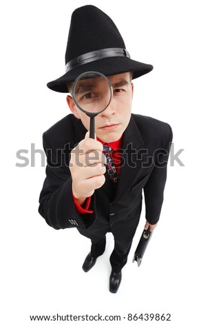 Young detective with briefcase, looking up through magnifying glass - stock photo