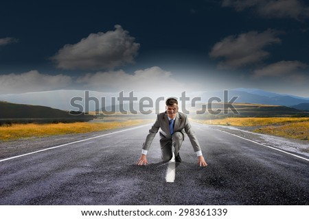 Young determined businessman standing in start position
