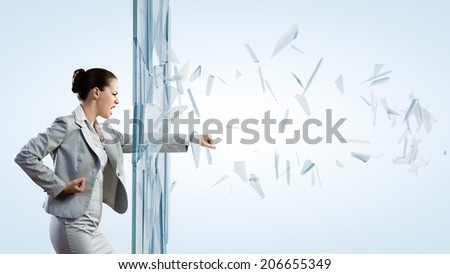 Young determined businesswoman breaking glass with karate punch - stock photo