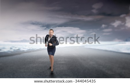 Young determined businesswoman competitor running on road