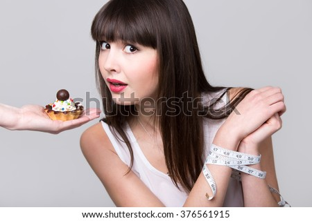 Young dieting woman with hands tied with measurement tape sitting in front of tart cake, got caught while trying to reach it and take a bite, studio, gray background, isolated - stock photo