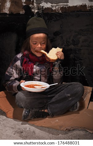 Young dirty homeless boy eating on the street sitting on cardboard - stock photo