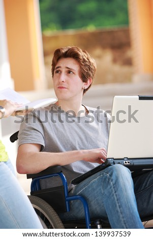 Young disabled boy and his female friend studying together - stock photo