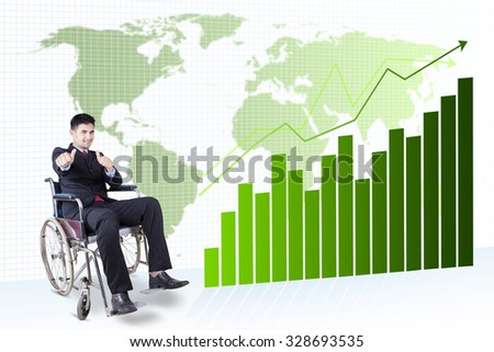 Young disabled entrepreneur sitting on the wheelchair and showing thumbs up in front of financial chart background - stock photo
