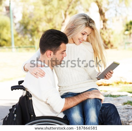Young disabled man and his girlfriend with digital tablet - stock photo