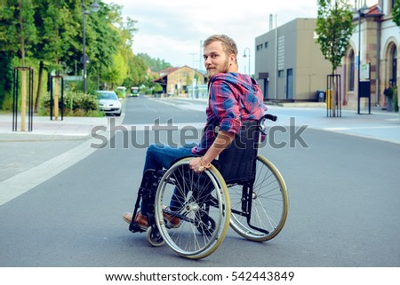 young disabled man in wheelchair on road