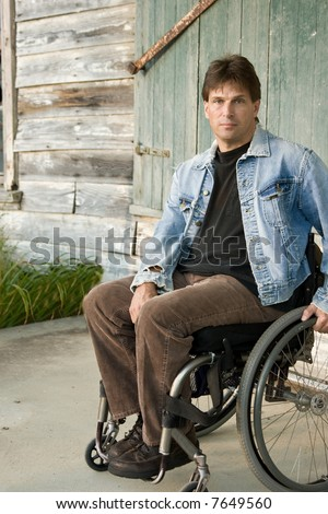 young disabled man in wheelchair, portrait - stock photo