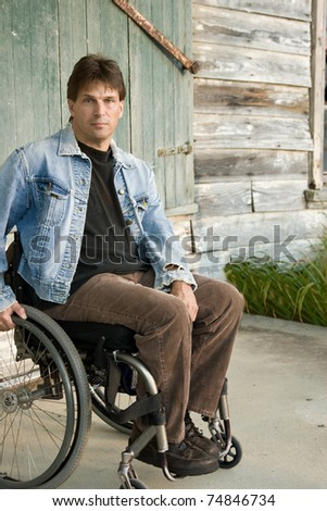 young disabled man in wheelchair with determined look - stock photo