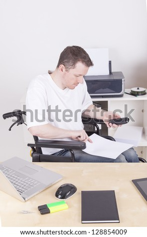 young disabled man in wheelchair working in a home Office. - stock photo