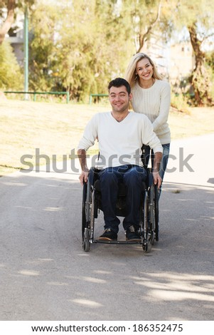 Young disabled man on a wheelchair walking with his girlfriend in the park - stock photo