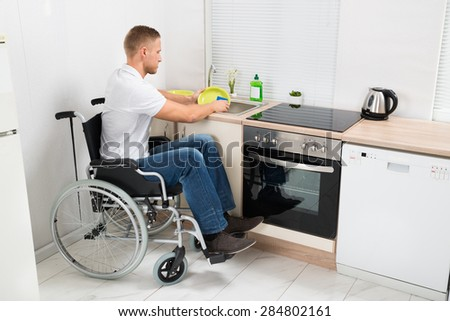 Young Disabled Man On Wheelchair Washing Dishes In The Kitchen - stock photo