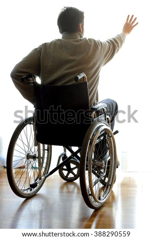 young disabled sitting in a wheelchair in the room and he opens the window - stock photo