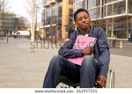 young disabled student sitting in a wheelchair  holding folders - stock photo