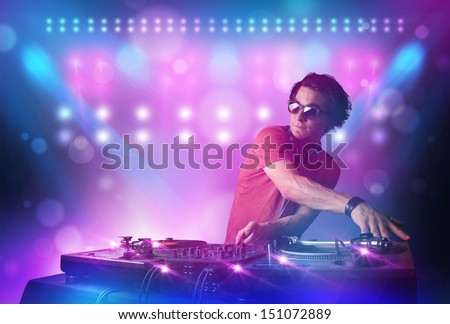 Young disc jockey mixing music on turntables on stage with lights and stroboscopes - stock photo