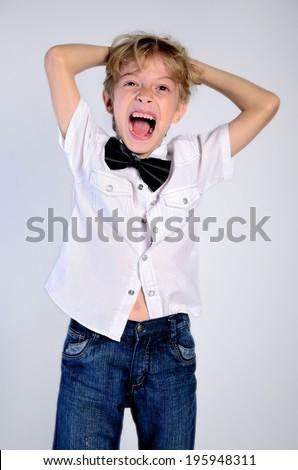 Young disheveled boy on grey background - stock photo