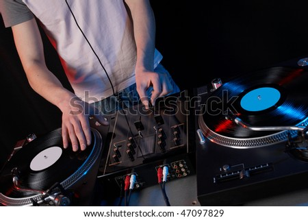 Young disk jockey for the vinyl disks and mixer in club