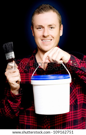 Young DIY home owner holding up a tub of paint and a brush as he smiles in anticipation of redecorating and renovating his house - stock photo