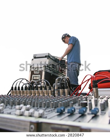 Young dj mixing on a snowboard event outdoors. City scene - stock photo