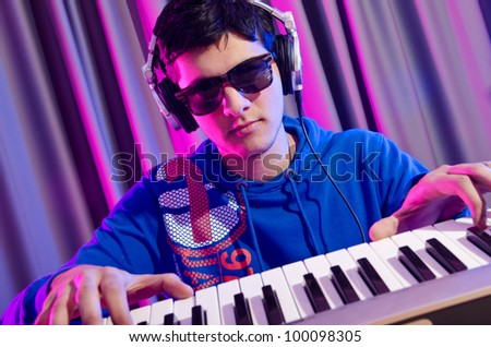 Young DJ playing his music - stock photo