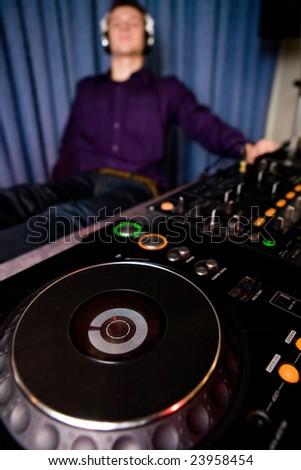 Young DJ relaxing in a nightclub - stock photo